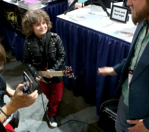 Budding guitarist checking out the goods during the 2015 NAMM show (Photo by Jesse Grant/Getty Images for NAMM)