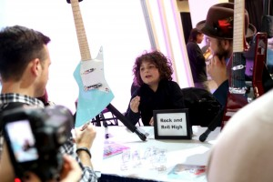 "Young musician talks ""guitars"" with NAMM attendees (Photo by Jesse Grant/Getty Images for NAMM)"